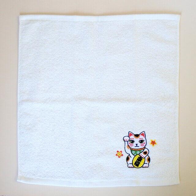 招き猫の刺繍が施されたハンドタオルの全体イメージ by コイトネコ