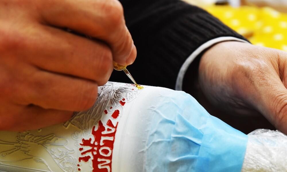 彫刻したボトルに職人が手作業で着色する様子 by ボトル彫刻サービス「tekizami-てきざみ-」