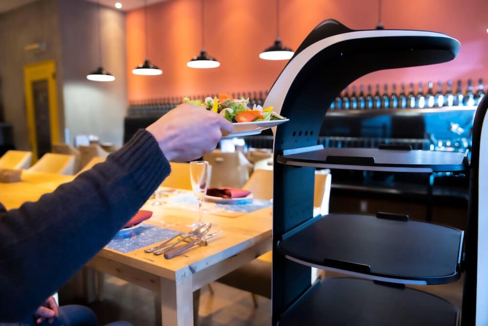 ネコ型配膳ロボット「BellaBot(ベラボット)」が配膳した料理を手に取るお客のイメージ