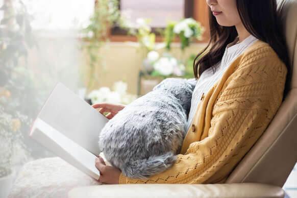 猫型クッション「MeowEver(ミャウエバー)」でお腹を温めながら読書をするイメージ
