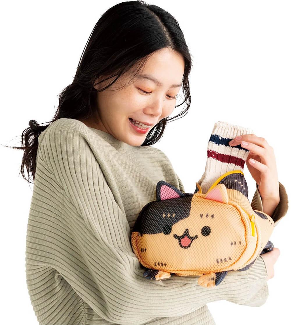 「香箱座り猫のお洗濯ポーチ」の中に洗濯物を入れるイメージ