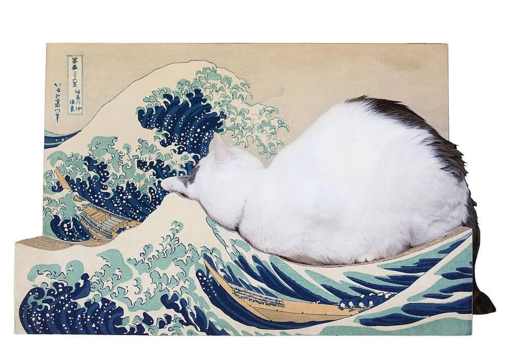 葛飾北斎の浮世絵「冨嶽三十六景 神奈川沖浪裏」をモチーフにした爪とぎで寝転ぶ猫
