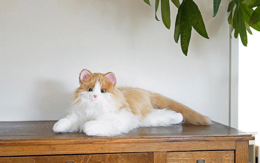 家具の上でくつろぐ猫型ペットロボット「しっぽふりふり あまえんぼうねこちゃん」ミックスブラウンカラー