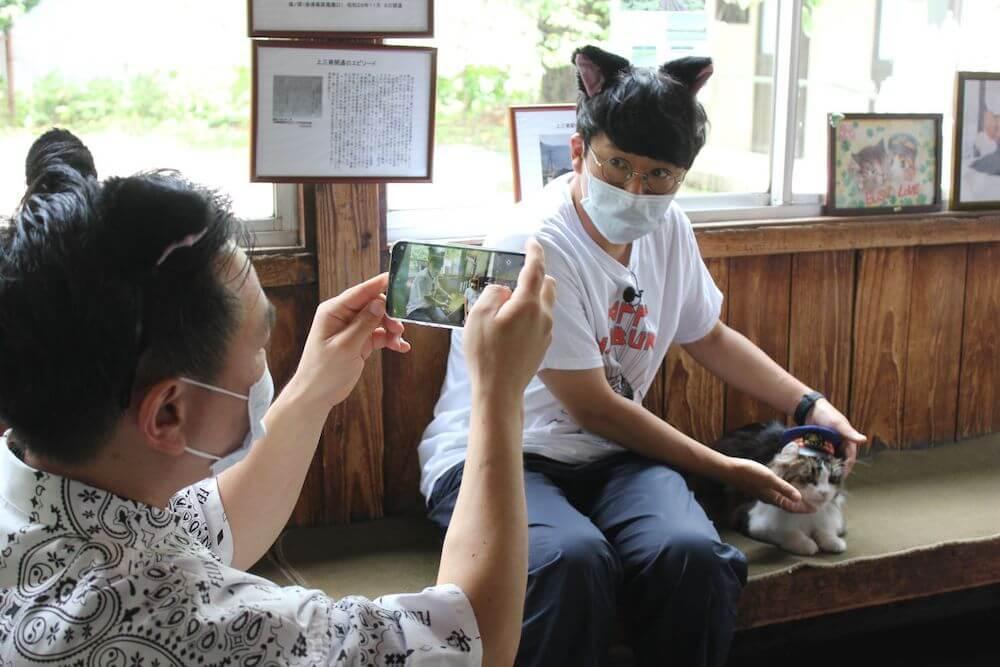 芦ノ牧温泉駅で働く人気の猫「らぶ駅長」と一緒に写真を撮るミキの亜生