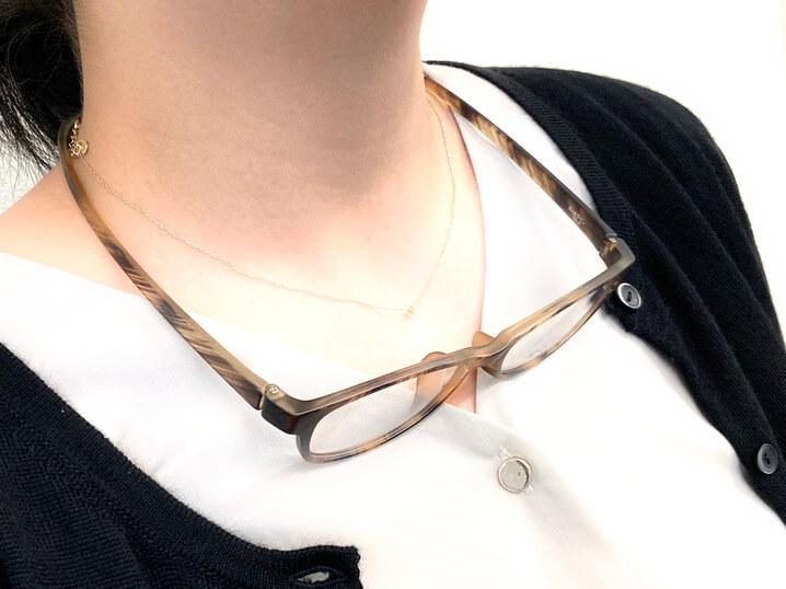 猫モチーフの眼鏡「にゃんブラン」を首にぶら下げたイメージ by メガネの愛眼